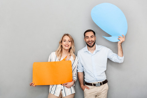 Attractive happy young couple standing isolated over gray background, holding empty speech bubbles